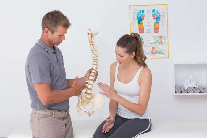 Chiropractor explaining back pain to patient